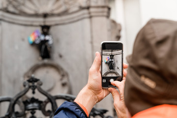 Brusseles, Belgium - May 2019:  a tourist takes pictures of a pissing boy dressed for the LGBT festival on a smartphone