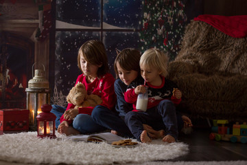 Three children, boy brothers, reading a book at Chrismas night