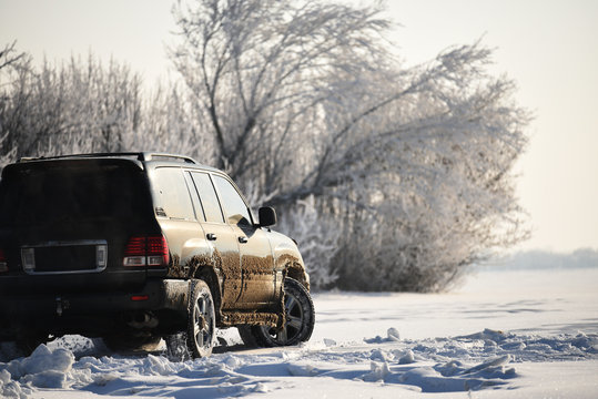 An SUV car riding in a field covered with snow off-road.