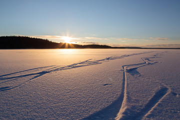 Zig-zag traces of ice-skates on pure snow-covered surface of the lake at beautiful sunset.