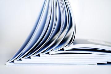Stack of open books on a white background, soft focus