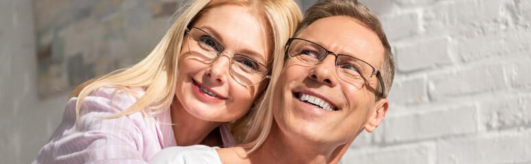 Panoramic shot of smiling couple in eyeglasses hugging at home