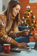 Happy woman doing online shopping for Christmas