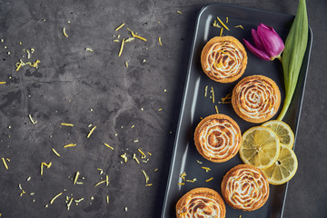 Modern french lemon tartelettes with a tulip on dark background