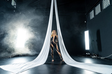 Beautiful flexible woman gymnast with white aerial silks isolated on black background with smoke