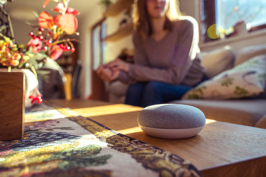voice controlled smart speaker with a woman in the background in a interior home environment.