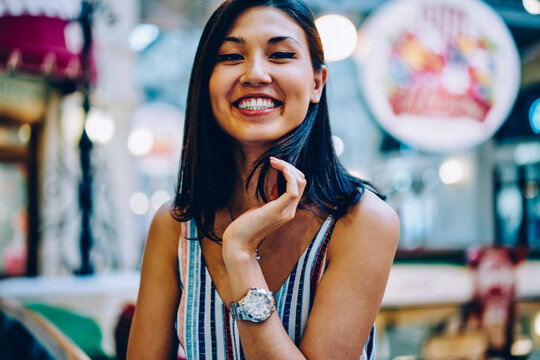 Selective focus on half length portrait of cheerful pretty asian girl feeling happy looking at camera, cute brunette young woman smiling enjoying leisure standing on blurred background indoors