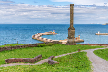 The Candlestick Chimney with the pier and the West Pier Lighthouse and North Pier Lighthouse in the background, seen in Whitehaven, Cumbria, England, UK