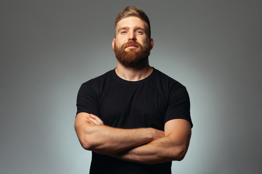 Fabulous at any age. Portrait of charismatic muscular 30-year-old man standing over dark gray background. Perfect haircut. Rocker, biker, hipster style. Copy-space. Studio shot