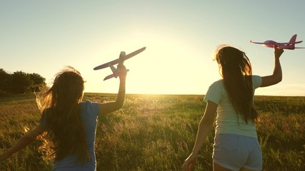Dreams of flying. Happy childhood concept. Two girls play with a toy plane at sunset. Children on background of sun with an airplane in hand. Silhouette of children playing on plane