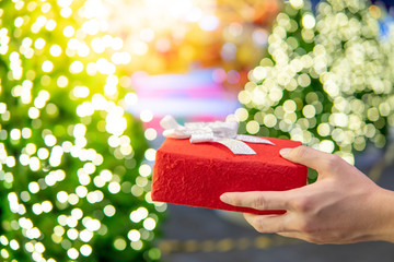 Male hand holding red Christmas gift box or New Year present with blurred illuminated decorative Christmas tree in the background. Decoration for festive season. New Year Celebration concept