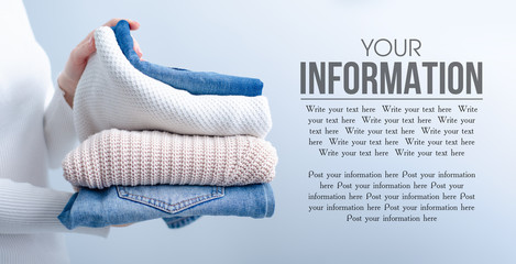 Stack of knitted clothes and jeans in female hands on grey blurred background, space for text Wall mural