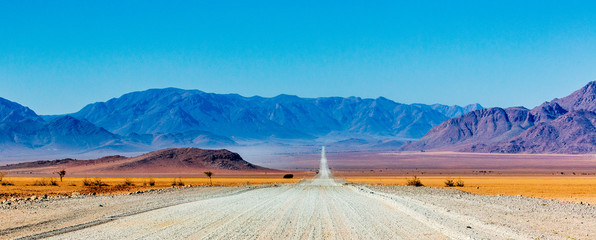 Deurstickers Blauw Gravel road in Namibia - panorama - Africa