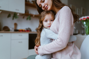 family scene, daughter hugs mom with an expression of anxiety or fear, mom has an expression of tenderness on her face