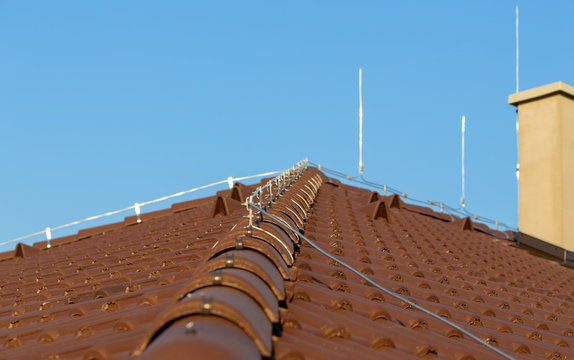 Tile roof with chimney and lightning protection system installed. Lightning rods. Close-up shot. Lightning conductor.
