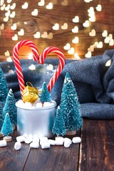 Christmas marshmallows and new year decorations on wood with grey plaid. Winter holidays