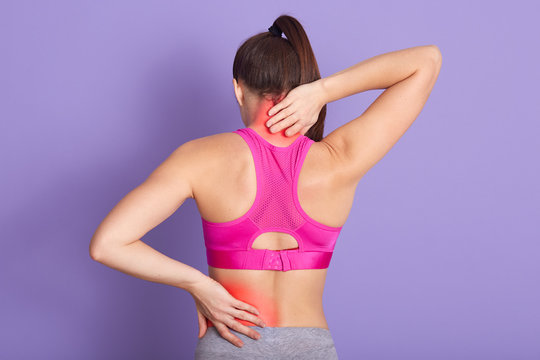 Woman with perfect body having painful muscle injury in lower back and neck. Fitness girl sport girl with sports injury posing backwards isolated over lilac background. Healthy care and fitness concep