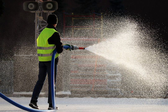 Worker watering from a hose outdoor. Jet spray of water in sunlight, concept of freshness and street cleaning