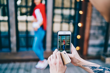 Cropped view of male hands with tattoo holding modern smartphone and focusing on young woman dressed in casual wear to make photo for blog.Taking picture of hipster girl standing outdoors on cellular