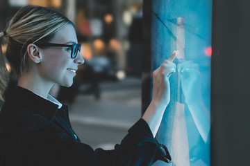 Smiling female standing at big display with advanced digital technology. Young woman touching with finger sensitive screen of interactive kiosk for find information while standing on street in evening