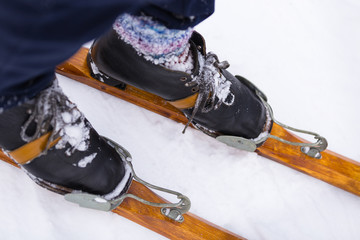 Man in multicolored knitted socks stand on a vintage wooden ski