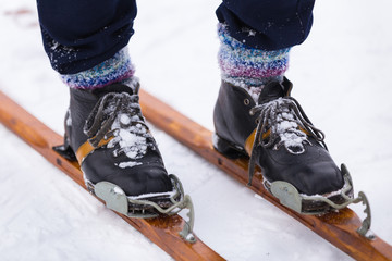 Male legs in multicolored knitted socks stand on a vintage wooden ski