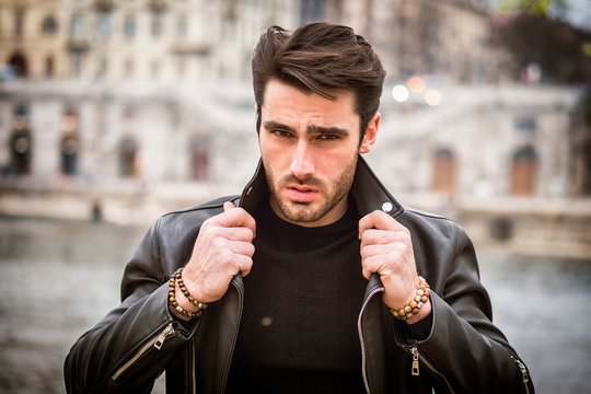One handsome young man in urban setting in modern city, standing, wearing black leather jacket and jeans, looking at camera