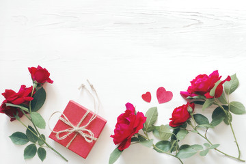 Romantic background with bouquet of red roses, heart symbols and red gift box on a white wooden background, top view