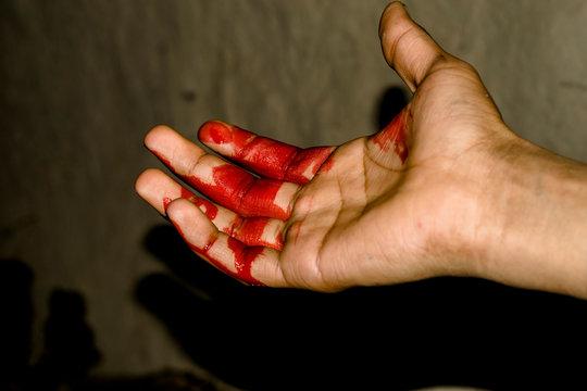 a badly bleeding hand and dark background
