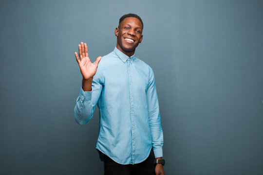 young african american black man smiling happily and cheerfully, waving hand, welcoming and greeting you, or saying goodbye