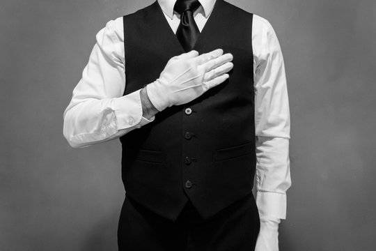 Black and White Portrait of Butler in Vest and White Gloves Holding His Hand Over His Heart. Concept of Service Industry and Professional Hospitality. Dependable Servant. Copy Space for Service.