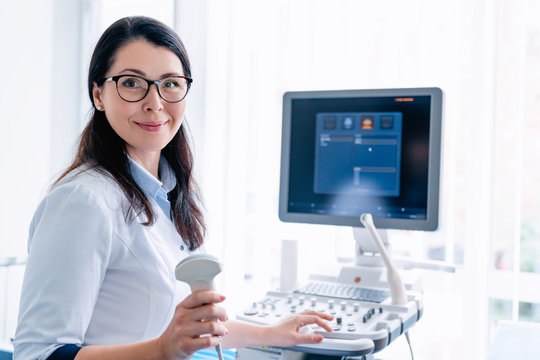 Portrait of cheerful female doctor with ultrasound sensor