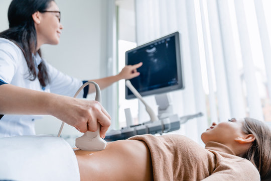 Mid adult female doctor using ultrasound scanner