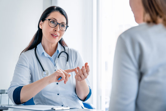 Smiling female doctor giving advice to female patient in cabinet