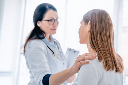 Woman medical doctor holding her hand on patient's shoulder