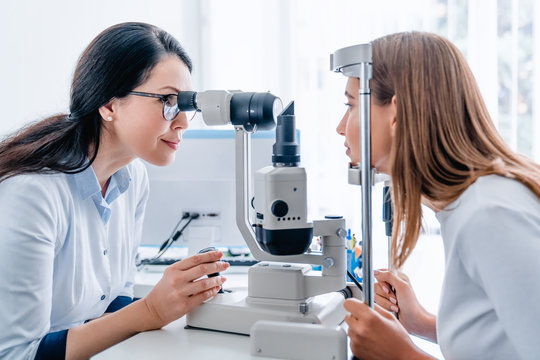Adult female doctor ophthalmologist checking eye vision of young girl in modern clinic