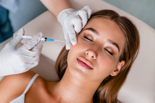 Young woman gets beauty facial injections in salon