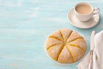Freshly baked carrot scones and white cup of tea with milk on light blue background. delicious homemade cakes