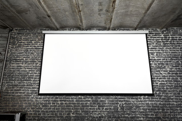 Image of white projector screen on grey brick wall.