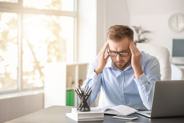 Young man suffering from headache in office