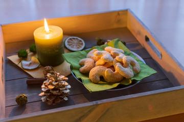 Teller mit leckeren vanillekipferl auf einem Tablett aus Holz bei Kerzenschein
