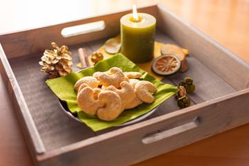 Teller mit vanillekipferl auf einem Tablett aus Holz mit Kerze und Weihnachtsdekorationen
