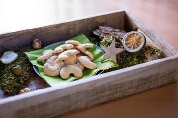 leckere vanillekipferl auf einem Tablett aus Holz mit Weihnachtsdekorationen