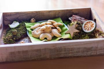 Teller mit vanillekipferl auf einem Tablett aus Holz zwischen Dekoration aus Moos