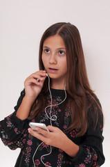 young girl has earphones in her ear, she speaks by phone, seh is very happy,