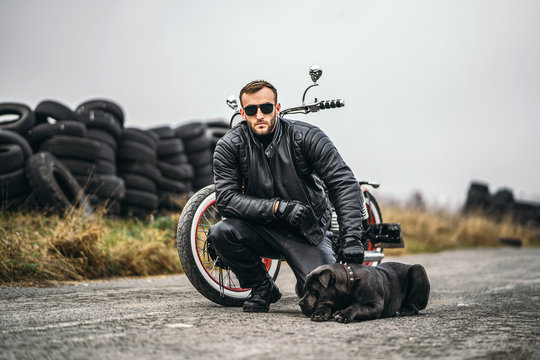 Biker in a leather suit crouched near his dog and red motorcycle on the road. Many tires on the background