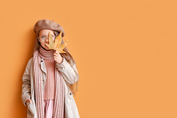 Fashionable little girl in autumn clothes on color background