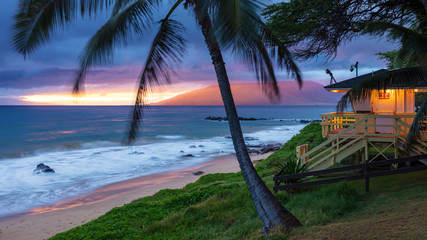 Papiers peints Palmier Kamaole Beach Sunset Maui. Sunset glow on the west Maui mountains, swaying palm trees in the tropical breeze, waves crashing on the sandy beach and the lifeguard hut illuminated ready for the the nigh