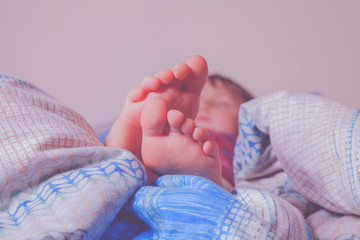 Retro styled image of beautiful feet of a little cute child girl in bed.  Sleep and relax concept.