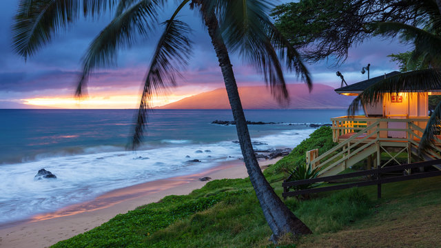 Kamaole Beach Sunset Maui. Sunset glow on the west Maui mountains, swaying palm trees in the tropical breeze, waves crashing on the sandy beach and the lifeguard hut illuminated ready for the the nigh